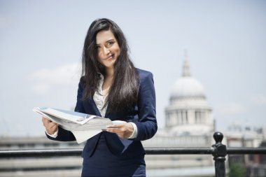 Indian businesswoman holding newspaper