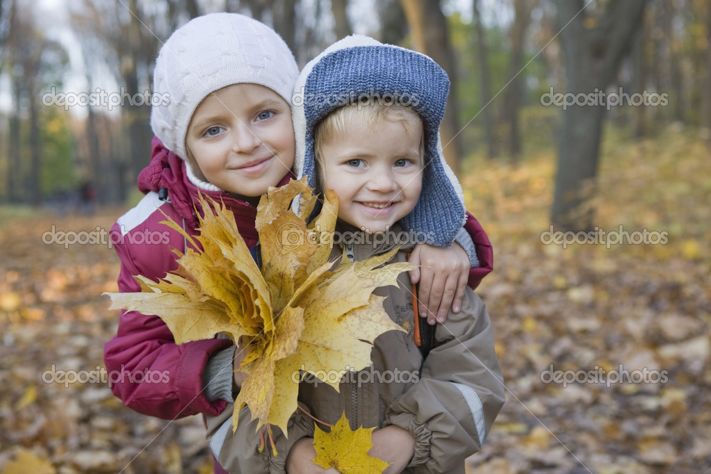 Brother and sister holding leaves