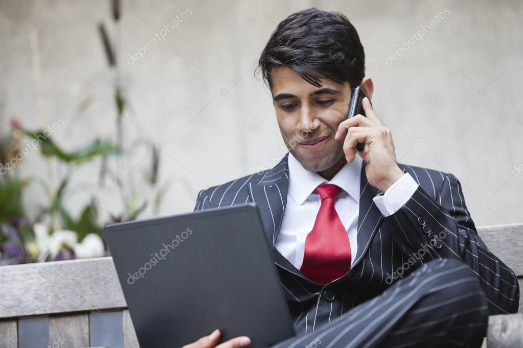 An Indian businessman using tablet PC while communicating on cell phone