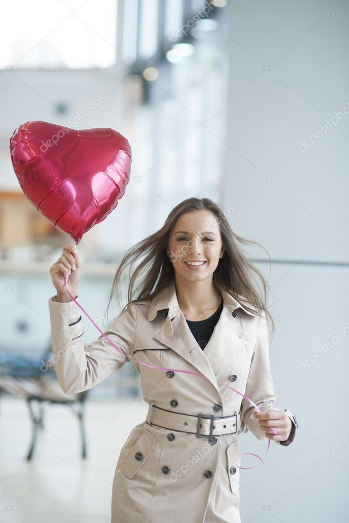 Businesswoman holding heart shaped balloon