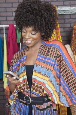 Fashion designer reading text message on cell phone