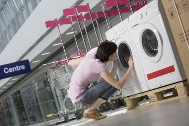 Young woman looks inside tub of washing machine