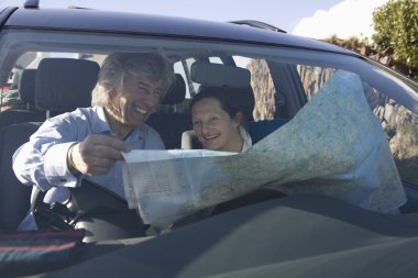 Senior couple with  map in car