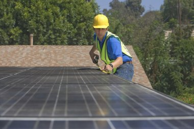 Maintenance worker measures solar array on rooftop