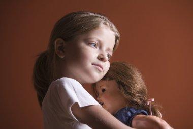 Girl embracing doll