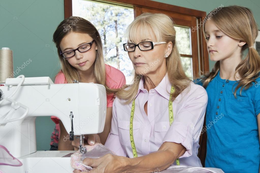 Granddaughters with grandmother sewing cloth