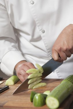 chef slicing cucumber at kitchen