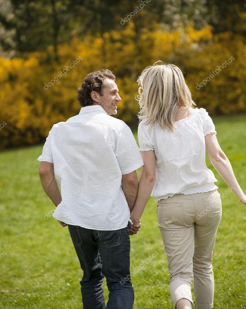 Couple running through park