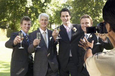 Man taking a picture of five men toasting with wine glasses at wedding party stock vector