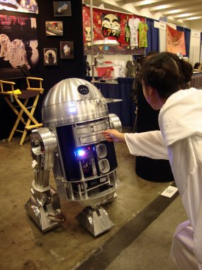 Woman Dressed as Princess Leia reaches out to touch R2-D2 replic