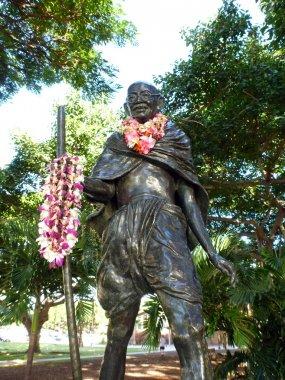 Statue of Mahatma Ghandi holding a walking stick and wearing rea