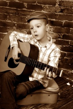 little boy playing guitar in vintage style