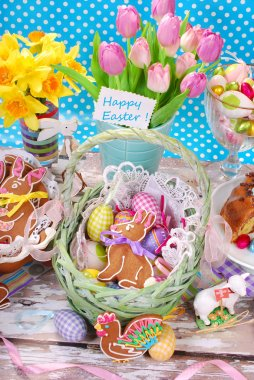 easter basket with eggs,gingerbread bunny and fresh tulips