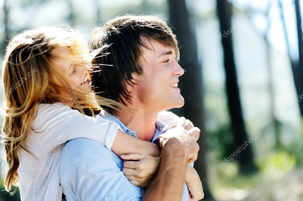 Carefree couple have fun embracing and playing outdoors in the sunlight. a real couple, real emotions, real love.