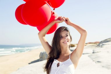 Beautiful girl with red ballons sitting in the beach stock vector