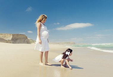Pregnant woman and her daughter on the beach