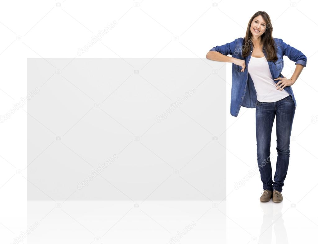 Beautiful woman standing over a blank billboard, isolated over a white background