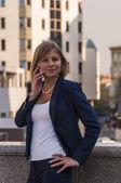 Mladá žena v modrém obleku podnikatel mluví do mobilu na pozadí moderní obchodní centrum