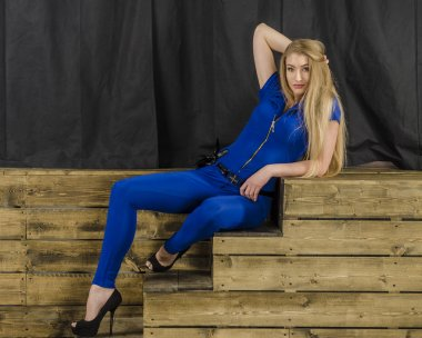 Beautiful long haired blonde in blue overalls and high heels sitting on wooden stairs