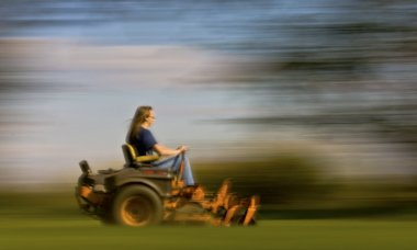 Male cutting the grass on expansive lawn using yellow zero-turn mower