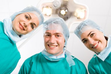 Happy doctors looking at patient after successful surgery