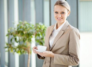 Beautiful young white collar worker having coffee during break