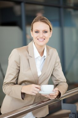 Beautiful female white collar worker having coffee break at work