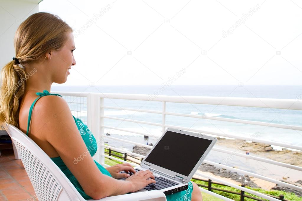Young woman using laptop on balcony