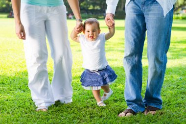 Cute baby girl walking with parents