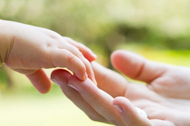 Caring mother and baby's hands