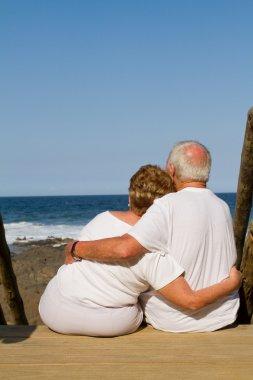 Rear view of senior couple cuddling