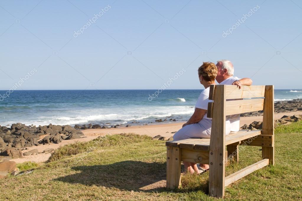 Senior couple sitting on beach bench