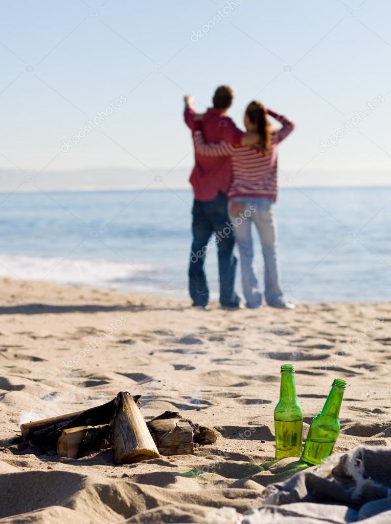 Young couple relaxing on beach, focus on bonfire and beer bottle