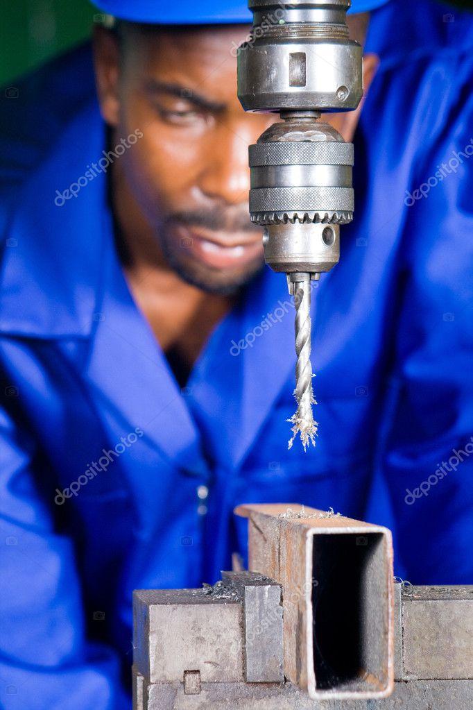 African blue collar worker in workshop working on drilling machine