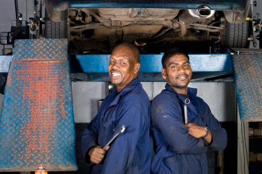 Two african american mechanics inside garage