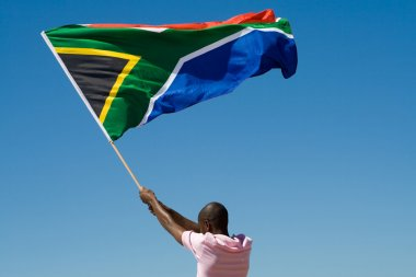 African man waving a south african flag against blue sky