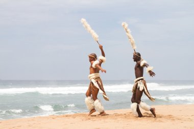 Two african zulu men dancing on beach