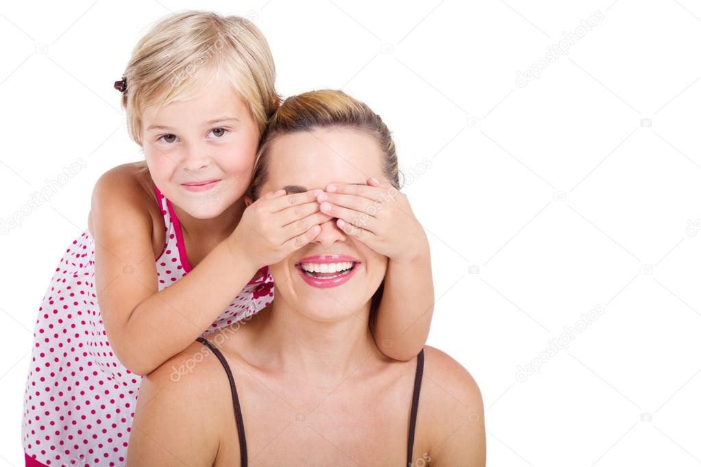 Playful happy little girl covering her mother's eyes, studio shot isolated on white