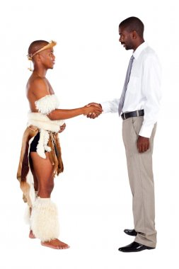 Modern and tradition: african tribesman handshaking with modern businessman