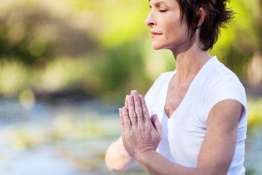 Middle age woman doing yoga meditation