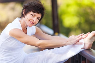 Beautiful middle aged woman stretching leg