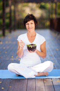 Healthy middle aged woman eating salad outdoors