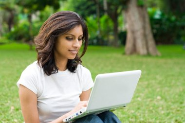 Young indian woman using laptop outdoors