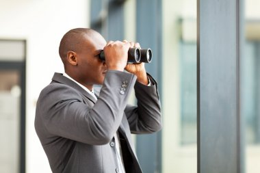 Determined african american businessman using binoculars in office