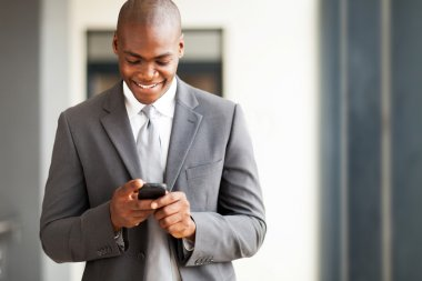 Young african american businessman reading email on smart phone