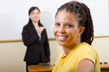 Adult african student in classroom, background is a teacher standing in front of white board