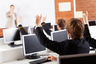 Group of high school students hands up in computer class