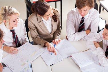 High school teacher tutoring group of students in classroom