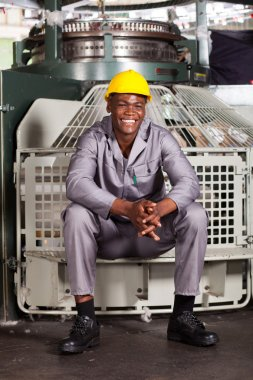 Happy african american textile worker sitting on machine
