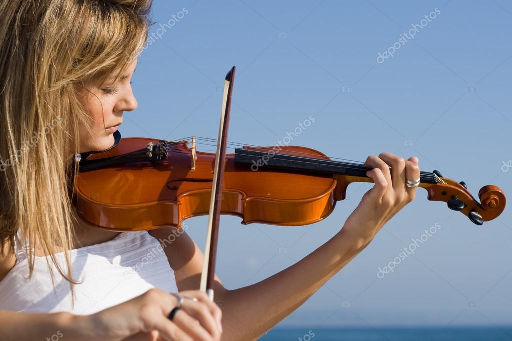 Pretty young female violinist practice on beach